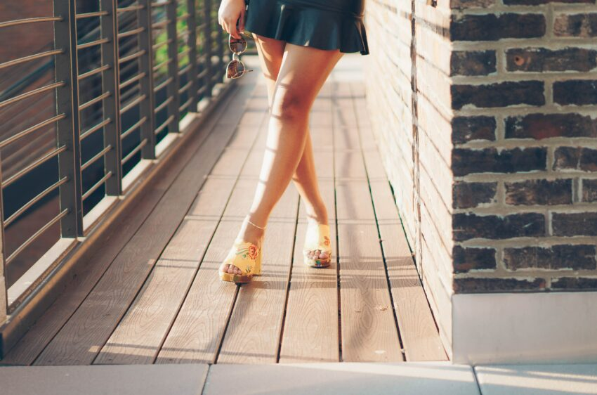 woman crossing leg while standing on hallway during daytime